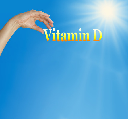 Take your Vitamin D - Sunshine and blue sky background with the word Vitamin D and a female hand positioned over the V with plenty of copy space below