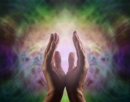 manos abiertas: sanador pránico con hermosa Aura - multicolor campo complejo de la energía viñeta con las manos masculinas alcanzan para arriba y una luz de color rosa suave entre Foto de archivo