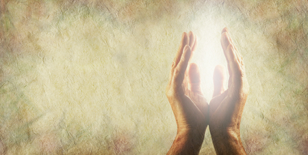 open hands: Light worker Message Board Banner - Male hands parallel with a bright white light energy between on a rustic buff colored stone effect background with copy space on left