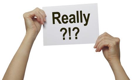 molesto: En realidad - una palabra con una multitud de significados - '?!? Realmente' par de manos la celebración de una hoja de papel con la palabra sobre un fondo blanco Foto de archivo