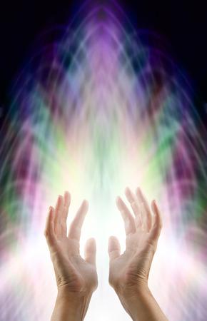 manos abiertas: la sensibilidad de energía - las manos femeninas en llegar hasta un campo de energía de la matriz multicolor con una ráfaga de luz blanca ascendente Foto de archivo