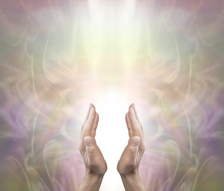 prana: Pranic Healer sending distant healing - Male parallel hands with a white light behind on a soft ethereal misty muted color background and copy space