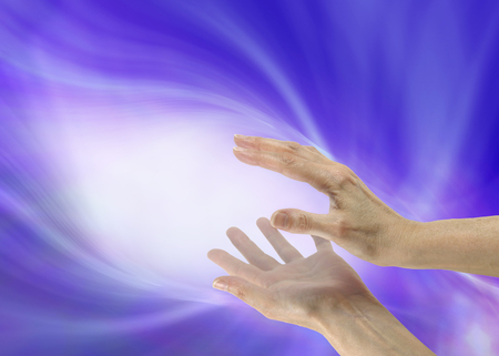 Sending healing energy - female hands with white light between, on a flowing linear blue purple  energy background with copy space Stock Photo