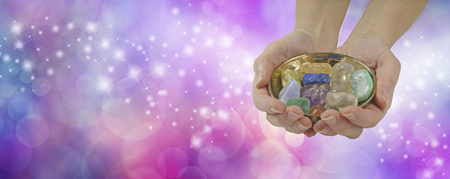 tumbled stones: Crystal healing therapist banner - female crystal healer holding and offering brass dish with a selection of healing crystals on a pink purple colored sparkling wide background with copy space Stock Photo