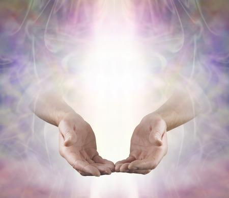 manos abiertas: Ofreciendo Usted amor angelical y Curación - las manos abiertas machos que salen de fondo hermoso campo de energía de colores apagados con un rayo de luz blanca y un montón de espacio de la copia arriba