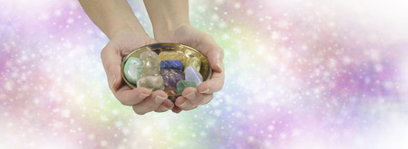 healer: Crystal healing therapist website header - female crystal healer holding and offering brass dish with selection of healing crystals on pastel rainbow colored sparkling wide background with copy space Stock Photo
