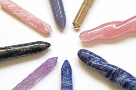 sodalite: 8 different healing crystal wands - a wheel spoke arrangement with an empty center displaying eight crystal wands including rose quartz, smokey quartz, amethyst, sodalite, lapis on white background