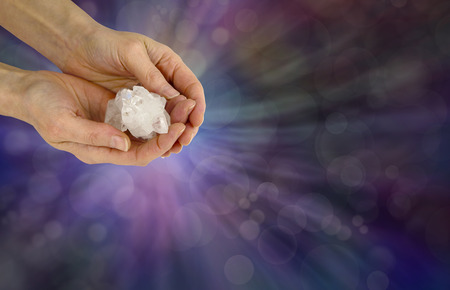 healer: Holding a Reiki Master Apophyllite Crystal Cluster  - female crystal healer holding a Reiki Master Apophyllite Crystal Cluster on a wide purple bokeh background with copy space