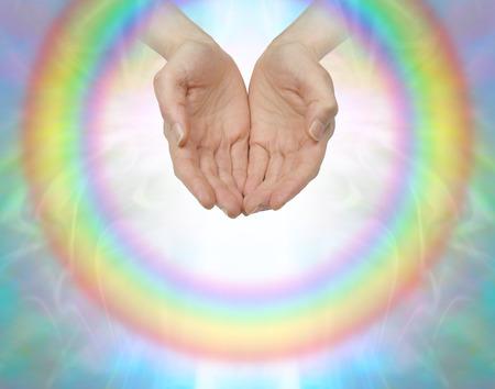 manos abiertas: Rainbow círculo de sanación - Mujeres manos ahuecadas rodeado por un arco iris circular transparente con una luz blanca interna sobre un fondo de color suave con espacio de copia