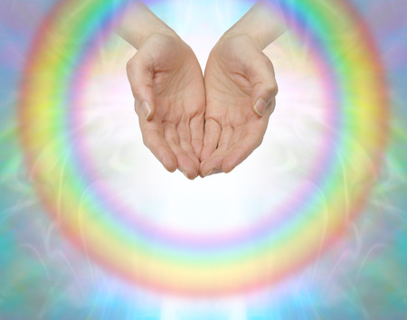 healing chi spiritual: Rainbow healing circle - female cupped hands surrounded by a transparent circular rainbow with an inner white light on a soft colored background with copy space