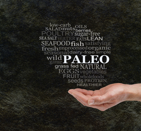 unprocessed: Consider The Paleo Diet - Chunky male hand with cupped palm  and a PALEO word cloud floating above on a dark stone cave wall effect background with copy space