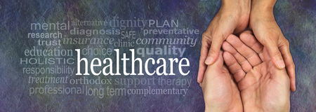 health care decisions: Health Care worker - female hands gently cradling male hands on a rustic dark stone background with a healthcare word cloud to the left