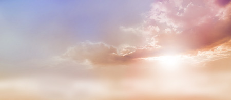 Dreamy Romantic Sky scape - beautiful wide peach and dusky pale blue sky and cloud scape with a burst of sunlight emerging from under the cloud base with plenty of copy space