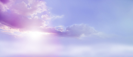 cloud scape: Romantic Lilac Sky scape - beautiful wide lilac and pink clouds lue sky and cloud scape with a burst of sunlight emerging from under the cloud base with plenty of copy space