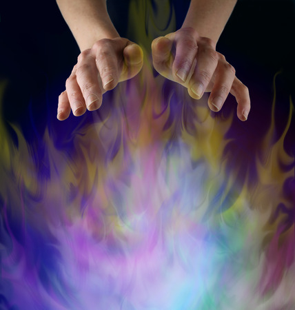 healing chi spiritual: Sensing Supernatural  Energy - female hands hovering above a multicolored gaseous misting energy formation on a black background with plenty of copy space below Stock Photo