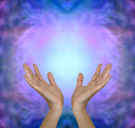 prana: Sensing Angelic Healing Energy - Female hands reaching up into a pink blue Angelic healing energy field with plenty of copy space above Stock Photo