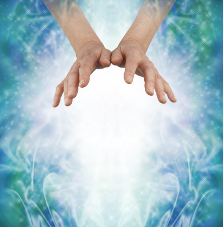vibrations: Sending out loving Chi Ki Qi Prana Energy - female hands hovering above a shaft of white wispy light and a sparkling swirling misty blue green energy formation background and copy space below Stock Photo
