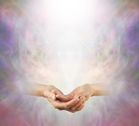 chi healer: Peaceful Meditation - a pair of female gently cupped hands with a shaft of white light above on a misty ethereal wispy background providing plenty of copy space