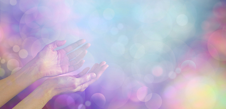 healing chi spiritual: Supernatural Phenomenon - female healing hands gently cupped up facing towards an ethereal blue white light orb on a muted multicolored bokeh background with plenty of copy space