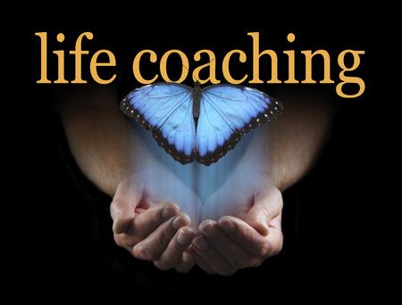 人生のコーチは-男性の手をカップ状の人生コーチング言葉に向かって立ち上がり大きな青い蝶と黒の背景から新興の軽いタッチ