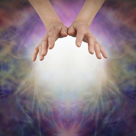 manos abiertas: Al sentir Prana con las manos abiertas - manos de una mujer flotando por encima de una bola de luz blanca sobre un fondo hermoso energía formación de niebla de colores vivos y copia espacio por debajo Foto de archivo