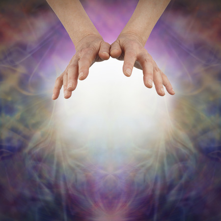 Sensing Prana with open hands - female hands hovering above a ball of white light on a beautiful richly colored misty energy formation background and copy space below Banque d'images