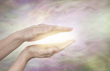 healing chi spiritual: Golden healing aura - female hands held in parallel position with a golden glow between on a subtle  radiating light energy field streaming outwards with copy space