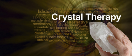 terminated: Crystal Therapy Word Cloud - Female hand pointing a clear quartz terminated crystal surrounded by a CRYSTAL THERAPY word cloud on a rich dark golden spiraling  vortex background