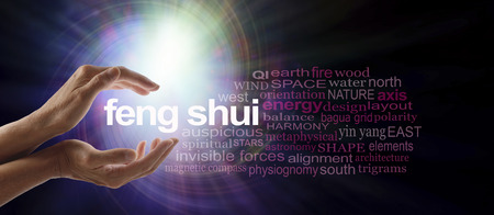 Shedding light on Feng Shui - Female hands cupped around the words FENG SHUI surrounded by a relevant word cloud with a spiraling bright light vortex behind photo