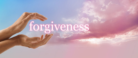 absolution: Forgive and release to your Higher Power - female hands gently cupped around the word FORGIVENESS on a soft blue sky background with a beautiful fluffy pink cloud stream and sun light Stock Photo