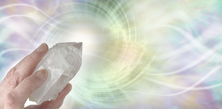 spiraling: Crystal Therapy Resonance - Female hand pointing a clear quartz terminated crystal upwards on a light pastel rainbow colored  spiraling  vortex background with copy space