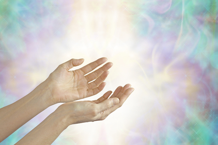 prana: Energy healer with open hands - female hands sensing life force energy with open palms on a beautiful pastel misty energy formation background Stock Photo