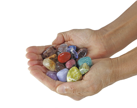 tumbled stones: Choose the stones you are attracted to - Female  cupped hands full of tumbled multicolored healing crystals on a white background Stock Photo