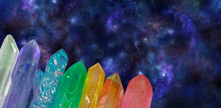 crystal therapy: Deep Space Cosmic Aura Wands - wide dark blue outer space background with seven chakra colored crystal wands spanning bottom left corner diagonally providing plenty of copy space above Stock Photo