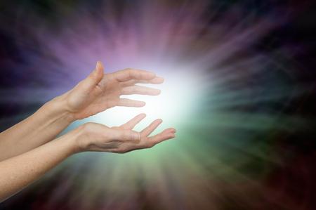 色の癒しエネルギー - 白色発光で虹の球と女性の手を晴れやかな色の光外側周り暗いビネット背景とコピー領域に