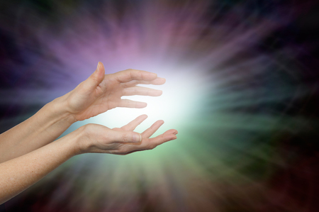 Beaming Color Healing Energy - female hands with a ball of white light emitting rainbow colored light outwards on a dark vignette background and copy space around