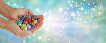 tumbled stones: Which Stone attracts you - Female  cupped hands full of tumbled multicolored healing crystals on a pale jade green bokeh background with streams of glittering sparkles and copy space Stock Photo