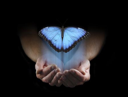 保つことができないいくつかの事がある - 男性は上記のコピー スペースで立ち上がり大きな青い蝶と黒の背景から浮上してカップを手 写真素材 - 63224531