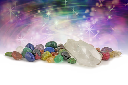chakra energy: Magical healing crystals - large clear crystal terminated quartz speciment surrounded by a selection of chakra colored healing crystals on a magical purple and green background with plenty of copy space Stock Photo