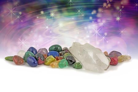 cristaux magiques de guérison - grand spécimen de cristal clair de quartz terminé entouré par une sélection de chakra couleur guérison cristaux sur un fond violet et vert magique avec beaucoup de copie espace