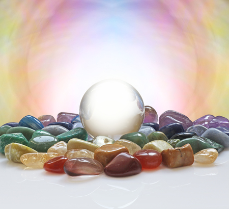 scrying: Crystal ball surrounded by healing crystals - large clear crystal ball with a selection of chakra colored healing crystals and a pastel colored background plus plenty of copy space