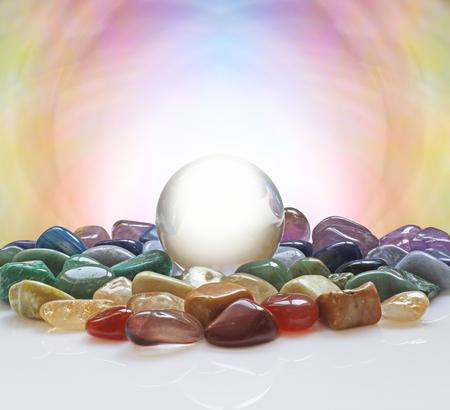 Kristallen bol omgeven door helende kristallen - grote heldere kristallen bol met een selectie van gekleurde chakra healing kristallen en een pastelkleurige achtergrond plus veel ruimte exemplaar Stockfoto - 63903927