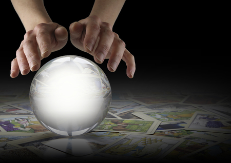 Crystal Ball Reading and Tarot Cards - Hands hovering over a large clear Crystal Ball on a dark background with tarot cards scattered randomly beneath and copy space to right