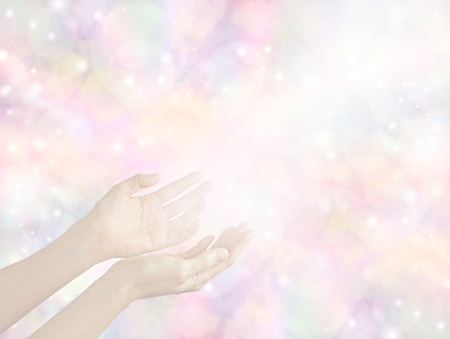healing chi spiritual: Sending Divine healing energy - female hands held out with a stream of white light on a soft pale pastel bokeh multicolored background with copy space all around