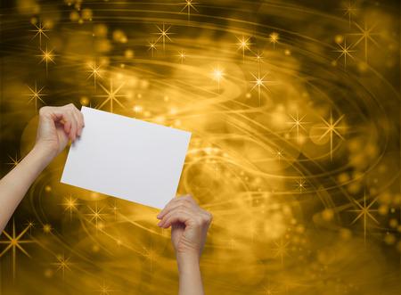 placa bacteriana: Celebrar Placa de Oro - manos de una mujer sosteniendo una tarjeta de promoción en blanco blanca en un profundo líneas marrones y dorados silbante y estrellas espumosos fondo
