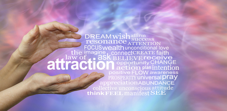 The Law of Attraction Word Cloud - female hands with the word ATTRACTION floating between surrounded by a relevant word cloud on a pink and blue misty wispy energy formation background Stock Photo