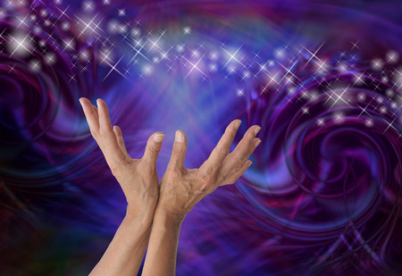 spiraling: Sensing Supernatural Electromagnetism - Female energy worker with hands outstretched and open upwards towards stream of sparkles on a dark machine-like spiraling  formation background