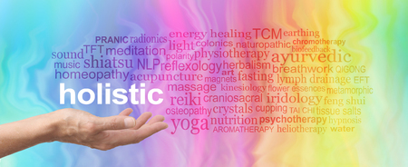 Holistic Therapy Word Cloud - female hand held palm up the word HOLISTIC in white above surrounded by a relevant word cloud on a rainbow colored marble effect background