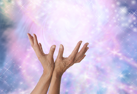 Sensing magical healing energy - Female energy worker with hands outstretched and open upwards sensing spectacular healing energy of gently sparkling pink and blue light streams Stock Photo