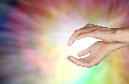 prana: Spiraling Healing Energy - female hands held in gently cupped position with a spiraling swirl of colors behind and radiating white light streaming outwards with copy space on left side